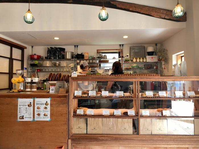 """鎌倉・坂の下は、パン好きならご存知の通りパンとカフェの激戦区。recetteの食パン専門店「Bread Code by recette」や「cafe recette」、フレンチスタイルが魅力の「BoulangerieEnsemble」等などが軒を連ね、多くの人々が坂の下目移りしてしまいます。  「なみまちベーグル」も、坂の下の一角で人気を集める有名店。店名にある通り""""ベーグル""""の専門店。先に紹介した「力餅家」から徒歩すぐの路地裏、築100年を超える古民家を改装したカフェで、手作りベーグルを販売しています。  【カフェでは、特製ベーグルや、ベーグルサンドのプレート料理が、ドリップコーヒー等のドリンクと共に頂ける。(画像は、ベーグルが並ぶ、店内サービスカウンター)】"""