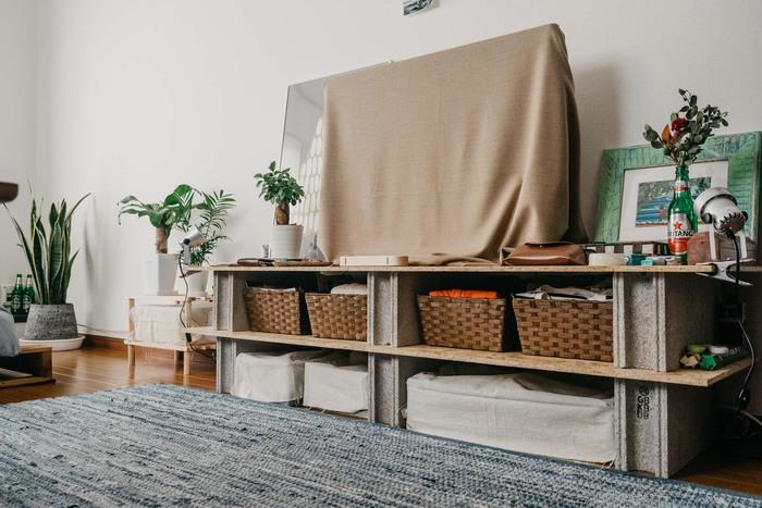 幅広めのテレビボード。棚板にはバスケットを置いて小物類を収納。トップの板にはテレビだけでなく、グリーンやお気に入りの絵を飾ってもいいですね。