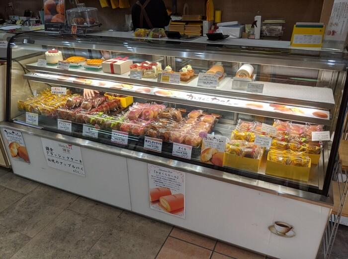 「鎌倉ニュージャーマン」は、創業1968年創業の老舗洋菓子店。都内や横浜市内、逗子や大船に店舗がありますが、店名にある通り、鎌倉駅東口の駅前に本店を構えています。  店内には、ショートケーキやロールケーキ、アップルパイ、といった洋生菓子、焼き菓子等が並んでいますが、一際目立つのは、やっぱり看板商品、鎌倉の中でもロングセラーを誇る『かまくらカスター』です。【店内ショーケースに並ぶ「かまくらカスター」】