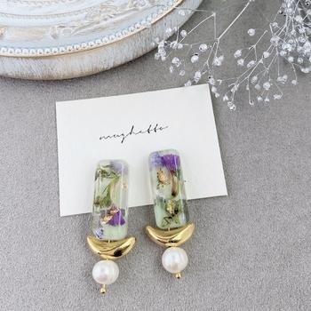スターチスなどの花をレジンで包んだ、繊細で美しいピアス。 淡水パールと三日月のパーツはアンティーク感があり大人っぽいデザインです。