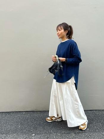 ブルーのトップスに、白のロンTをレイヤードしたスタイリングです。首元と裾からチラ見せすることで、トップスを一枚で着るよりもおしゃれ感がグッと高まります。白のフレアスカートでナチュラルにまとめつつ、足元はベージュのスニーカーでカジュアルさをプラス。