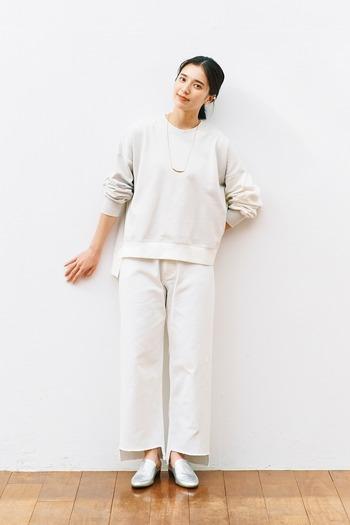 バイカラーのスウェットトップスに、白のワイドパンツを合わせた着こなしです。上下白系でまとめているので、カジュアルなスウェット素材もきちんと見えが叶います。足元はシルバーのシューズで、シンプルな着こなしを大人っぽく格上げ。