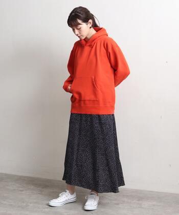 パッと目を引くオレンジのフーディー。カジュアルさを抑えるのにぴったりなネイビーのドット柄スカートを合わせて、大人っぽくまとめています。足元は、キレイめカラーに映える真っ白なスニーカーをチョイス。