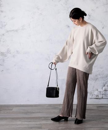 キナリカラーのゆったりスウェットに、ブラウンのプリーツパンツを合わせたコーディネート。黒のヒールシューズとショルダーバッグで、大人っぽくまとめています。ほどよいバランス感で、トレンド感たっぷりな着こなしですね♪