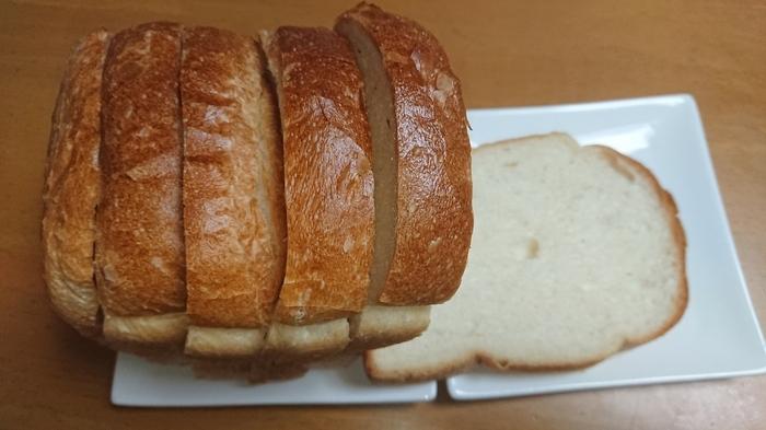 """持ち帰るのなら『山型食パン』がイチオシ。 先に紹介した「KIBIYAベーカリー」のものとは対極にある感じですが、天然酵母を使ってゆっくり発酵させているパン生地は、ふんわりとしてモッチリ。舌触りも滑らか。小麦の風味もあり、穏やかで優しい味わい。主張しすぎず、サンドイッチでも、トーストでも美味しい、シンプルで飽きのこない""""いつもの味""""です。コクと香りが良い『ごま食パン』も人気。"""