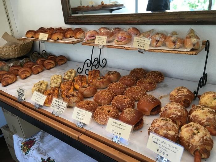 本格的なパンを良心的な価格で味わえる「ブランジェリー・べべ」は、極楽寺駅の改札口から徒歩1分程。住宅街の民家で商う、町のお洒落なパン屋さん。本格的なパンを良心的な価格で味わえると評判の、地元民が愛する人気店です。  【スウィーツ系からハード系まで種類豊富に店内に並ぶ。画像は、人気の『カレーパン』などが惣菜パンが並ぶ一角】