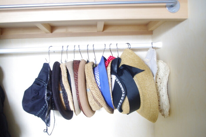突っ張り棒でクローゼット上部のデッドスペースを活用する収納術。つぶれやすい帽子も、こんな風に引っ掛けて収納できますのできれいな形を保てます。また、こだわりの帽子などは突っ張り棒を横に2本渡して、その上にディスプレイ収納することもできます。