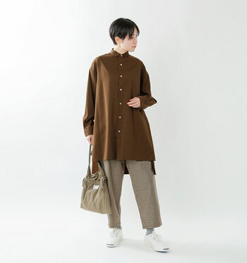 ブラウンのロング丈シャツに、ベージュ系のワイドパンツを合わせた同系色コーデ。バッグもベージュ系で合わせつつ、足元は白のスニーカーを合わせて爽やかに仕上げています。