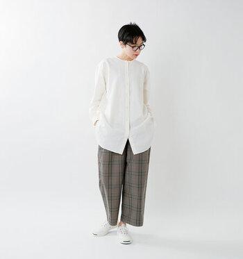 白のロング丈シャツに、チェック柄のワイドパンツを合わせたコーディネートです。すっきりとしたシルエットのトップスに、ワイドパンツでさりげないラフ感をプラスしています。足元はスニーカーで、大人カジュアルな印象に。