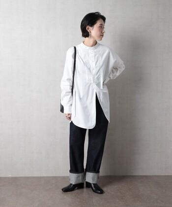 スタンドカラーの白シャツを、デニムのワイドパンツに合わせたスタイリング。足元を太めにロールアップして着こなしのポイントに。きちんと感のある黒のレザーシューズで、デニムを上品にコーディネートしています。
