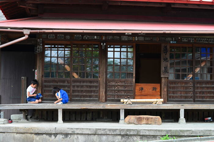 住環境は、そこで暮らす人々の意識や行動に大きな作用を及ぼすものですが、ここ「鎌倉」は、自然豊かな上、文化的な環境にあるためか、概ね人々の交流が健やかで穏やかです。  【極楽寺駅から徒歩2分程、極楽寺の門前、一般道路沿いにある「導地蔵堂(みちびきじぞうどう)」。一見すると民家のようなこの地蔵堂は、1267年に運慶作の地蔵像を安置したのがそのはじまりと伝わる由緒ある御堂である。中の地蔵像は、鎌倉二十四地蔵の一つに数えられている。広やかな縁台には、近隣の人々が思い思いに立ち寄る。】