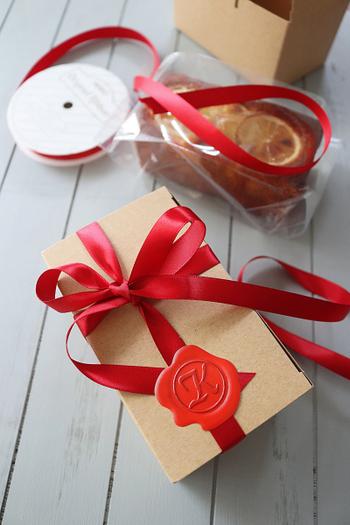 パウンドケーキを丸ごとプレゼントしたいときに。透明のパウンドケースに入れてからクラフトボックスに入れます。ゴージャスにリボンを巻いてシールを留めたら出来上がり。