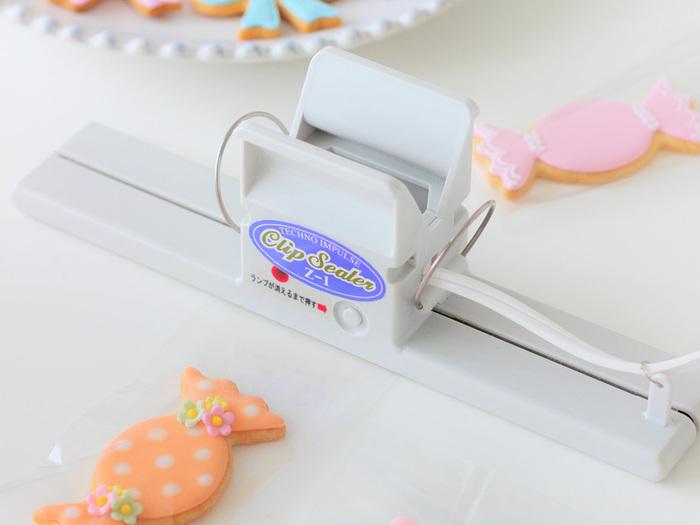 手作りお菓子のラッピングにあるとうれしい「クリップシーラー」。お菓子や食材の入った袋を熱で圧着して密封できる優れものです。20センチ幅のシールが可能。クリップの取っ手を握って口を開け袋を挟み、ランプが消えるまでボタンを押すだけの簡単操作。