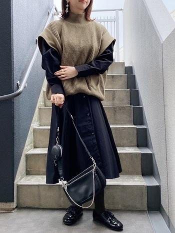 ハイネックのユニークデザインベストに、ハリのある黒のシャツワンピを合わせたレイヤードコーデです。襟と袖にボリュームがあるベストなので、ワンピースとバッグ、靴、タイツは黒をチョイスしてすっきりと。  かっちりとした靴とバッグできちんと感をプラスして、おでかけにも対応できるコーデに仕上がりました。