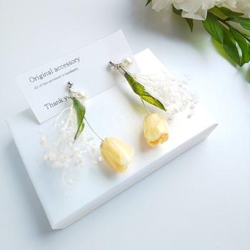 暖かくなってくる春に向けて耳元にも春を取り入れてみませんか?イエローのチューリップと繊細なかすみ草の組み合わせがブーケのような可愛らしいこちらのピアス!なんと花びらは本物のお花を使って立体的に重ね合わせ樹脂コーティングされたもの。サージカルステンレス製の金属アレルギー対応ピアスに変更可能です。