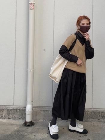 深めのアームホールで長めの袖のようにも見えるVネックベストとかわいらしいティアードシャツワンピのレイヤードコーデです。存在感のある白と黒の靴がアクセントに。  マスクも含めて、黒、白、ベージュの配色バランスが絶妙です。
