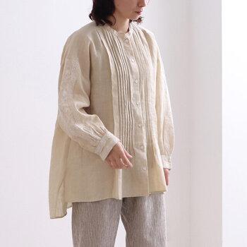 リネン素材を使用した、ピンタックデザインのブラウスです。ゆったり着られるシルエットと、白でさりげなくあしらった刺繍がナチュラルな雰囲気を演出しています。羽織りとしても活躍してくれる一枚です。