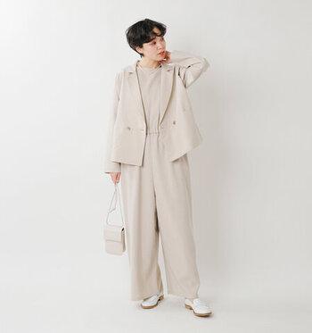 ベージュのテーラードジャケットに、同色のオールインワンを合わせたコーディネートです。ショルダーバッグも色を揃えて、白のフラットシューズで上品にまとめています。結婚式などのお呼ばれにも使える着こなしです。