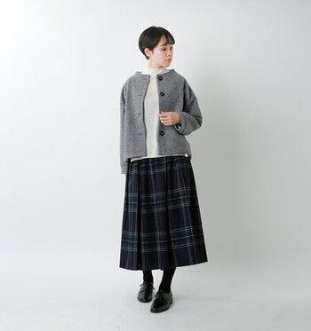グレーのノーカラージャケットに、チェック柄のスカートを合わせたスタイリング。トップスはシンプルな白をチョイスして、落ち着きのあるナチュラルコーデに仕上げています。黒タイツに黒のフラットシューズを合わせて、ほどよくシックな印象に。