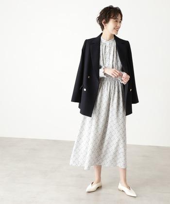 ダブルボタンのテーラードジャケットを、白の花柄ワンピースに羽織ったスタイリングです。甘さとクールさを兼ね備えた着こなしは、大人の女性にぴったり。足元は白のパンプスで、爽やかにまとめています。