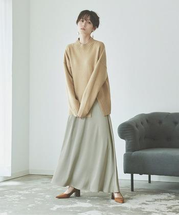 薄いグリーンのロングスカートに、ベージュのニットを合わせたコーディネートです。ニットはスリットが入ったデザインで、重さを感じさせません。足元はブラウンのヒールパンプスで、女性らしいテイストに仕上げています。