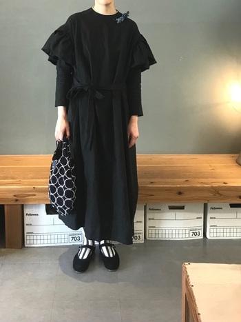 黒のワンピースをさらりと。袖がふわっとしていてデザインがとても可愛いので、黒でも重く見えません。首元のコサージュやストライプの靴下、ストラップシューズの小物遣いにもセンスが光ります。