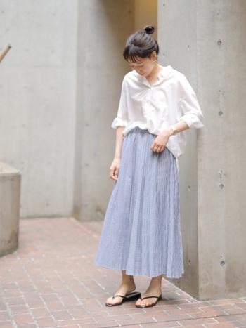 涼し気なブルーのプリーツスカートにイン。シャツは着崩してラフに着こなすのがお洒落のコツ。