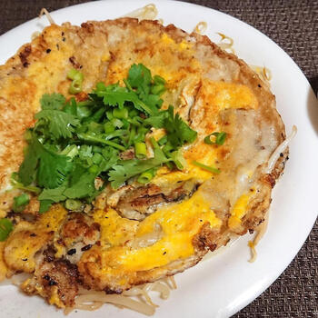 """ホイトートは、牡蠣のお好み焼きのような食べ物で、""""ホイ""""は貝、""""トート""""は揚げるという意味。揚げ焼きに近い油の量で、外はパリッと中はもっちり仕上げます。パクチーをたっぷりトッピングして召し上がれ。"""