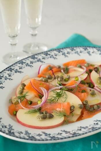 皮付きりんごとスモークサーモンを交互に彩りよく並べ、紫玉ねぎやピスタチオ・ケッパーなどを散らして。さっぱりとしておしゃれな前菜サラダが簡単にできあがります。