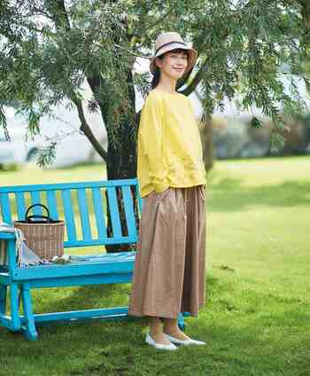 シロツメ草がデザインされた、パステルイエローのトップス。ベージュのロングスカートを合わせて、春らしい柔らかなコーディネートの完成です。季節感のあるハットと白のパンプスで、ナチュラルなスタイリングに。