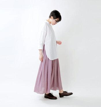 ピンクのサテンロングスカートに、白のブラウスを合わせたコーディネートです。サイドスリット入りのブラウスをチョイスしているので、シンプルな着こなしでもサマになります。足元はローファーシューズで、さりげなくきちんと感をプラス。