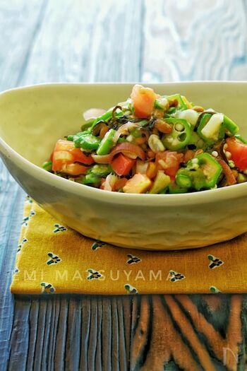 オクラとみょうがとトマトを納豆と合わせた和え物です。酢とごま油、砂糖でつくった調味液で混ぜ合わせています。  ごはんのお供や素麺の薬味にもぴったり。ねばねばのオクラと納豆が全体をうまくひとつにまとめてくれます。