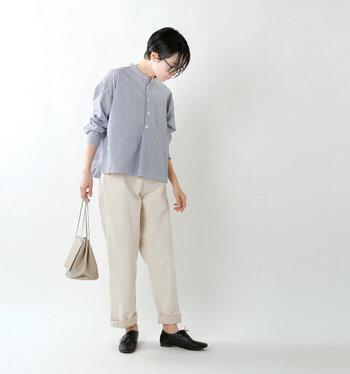 ホワイトデニムパンツに、ブルー系のシャツを合わせたシンプルなコーディネートです。パンツの足元をロールアップして、こなれ感をプラスしているのがポイント。ベージュのショルダーバッグと黒のローファーシューズを合わせて、全体的に落ち着いた印象の着こなしです。