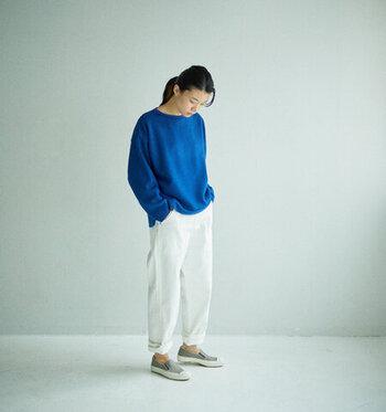 白のデニムパンツに、ブルーのトップスを合わせた着こなしです。足元はロールアップして足首を見せつつ、グレーのスリッポンでラフに仕上げています。パッと目を引く深みのあるブルーが、白デニムとも相性抜群のコーディネートですね♪