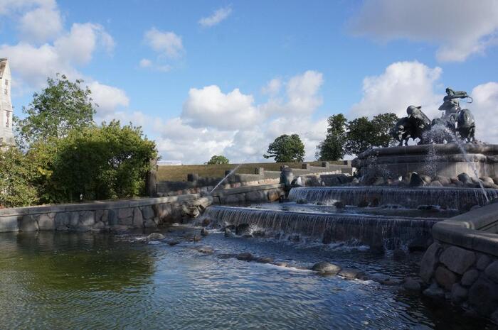 デンマークの首都コペンハーゲンにあるゲフィオンの泉。アクセスもよく、街中に現れるダイナミックな泉は人気の観光スポットです。北欧神話に登場するアース神族の女神の一人であるゲフィオンと、4頭の牛が大地を掘り起こしている像は迫力満点。