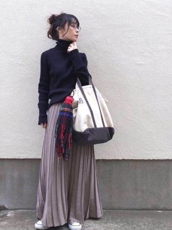 落ち着いた大人の雰囲気のあるバランスコーデ。綺麗なプリーツのマキシスカートで足を長く見せ、体のラインがわかる黒のタートルで上半身をキュッと引き締めることですらりとした印象に。バッグやスニーカーで絶妙な抜け感を。