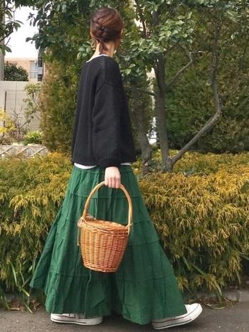 鮮やかなグリーンのティアードマキシスカートに、黒のバルーン袖ニット。綺麗なAラインと色のメリハリによってスタイルが良く見えます。トップスの丈感が短めで、インナーの白がチラリと見えているのも立体感が出ておしゃれですね。