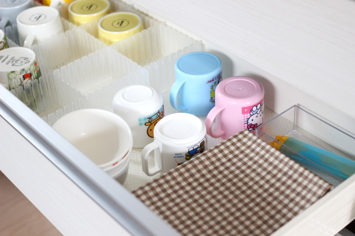 子ども用の食器は子どもが自分で取り出しやすい位置に収納。ランチョンマットや園へ持って行くお箸ケースなどもまとめてここへ収納して、自ら進んで用意できる方法にされています。