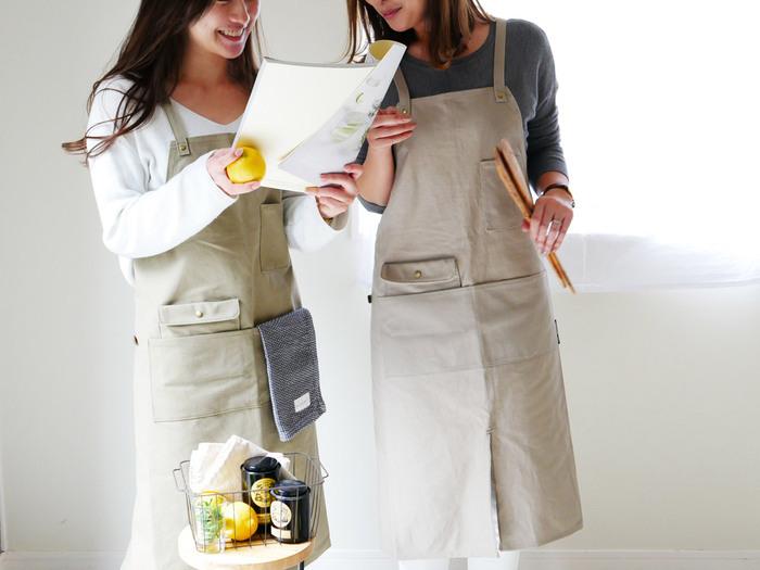 メンズライクなイメージのワークエプロンですが、こちらはシルエットがきれいで女性らしいデザイン。生地は丈夫なコットンキャンバスです。下部にスリットがしっかり入っているので動きやすくお料理だけでなくお掃除やガーデニングにも使えて便利。大きなポケットの他にレザー調タオルループがついています。タオルだけでなく、クリップやアルコールスプレーなどもひっかけておけますよ。