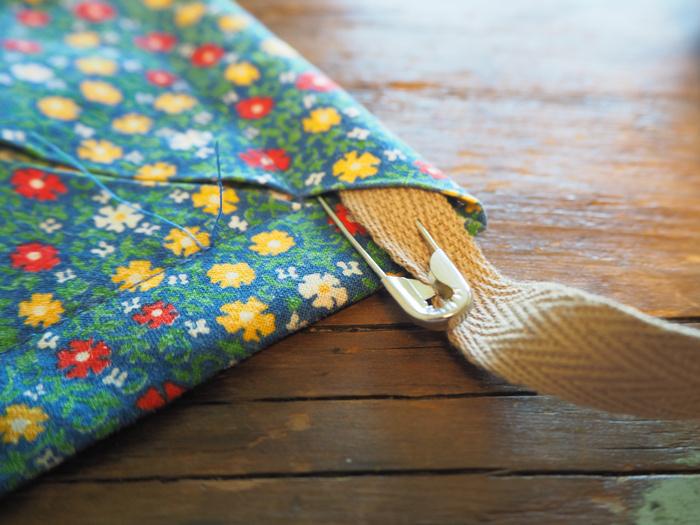 四方に2本のひもを通していきます。紐通しを持っていなくても安心してください!安全ピンで代用できます。太い紐を使うときは、端から2cmではなく紐が無理なく通る幅で縫いましょう。