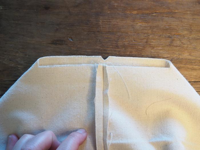 折りたたんでいたものを開いて、マチ部分を作ります。先ほどカットした部分と中央の縫い合わせたラインを合わせます。