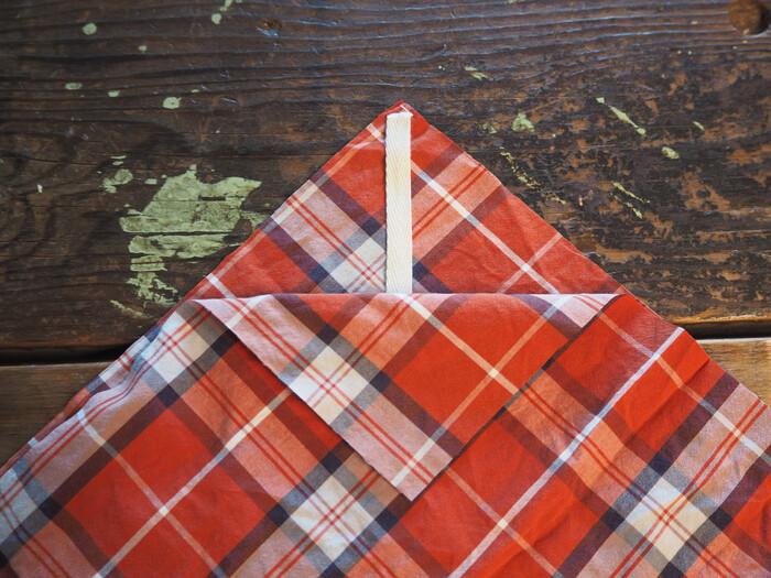 生地を中表にして対角線上に折りたたみます。この時、紐を写真のように挟んでおきましょう。