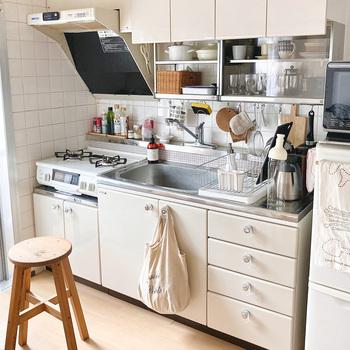 ナチュラルウッドやかご、布モノなど自然素材がよく映える白いキッチン。 ガラス風のレトロな取手がなんともかわいらしいですね。 小さな食器棚や天井いっぱいの天袋など収納もたっぷり。