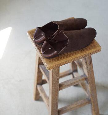 ルームシューズという名のレザースリッポンシューズです。AUTTAA(アウッタ)の代表作で、非常に人気が高い逸品。ルームシューズという名前がついていますが、外履きにも使えるようにソールもきちんと貼られています。  甲を覆うのは1枚革の独特な風合いのアッパー。毛足を潰して、オイルを染みこませ、つや消しをしたような表情を出しています。切り替えになったかかと側は、スムースレザーを採用。こなれた雰囲気を醸し出していますよね。