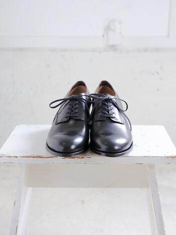 シンプルで、端正な表情が美しい外羽根のプレーントゥシューズです。かっちりとしたフォルムに高めのヒールを合わせ、すっきりとした大人の女性らしい足もとを実現してくれます。  カーフレザーを採用し、滑らかで艶やかな仕上がりに。フォーマルなコーデはもちろんのこと、カジュアルにも映えるきちんと感のある革靴です。