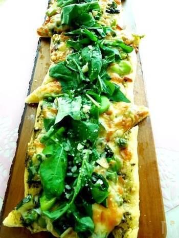 生地にジェノベーゼソースを塗り、さまざまなグリーン野菜をたっぷりのせて焼き上げる、すがすがしい色彩のピザ。最後に、ルッコラをたっぷりと。テーブルにみずみずしい美しさが映えますね。