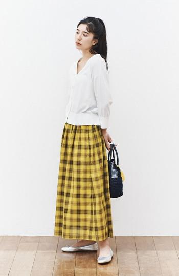 パッと目を引くイエローのチェック柄スカートに、白のカーディガンをトップス風に合わせた着こなしです。ナチュラルで素朴な雰囲気のコーディネートですが、シルバーのパンプス&黒のトートバッグが大人っぽく洗練された雰囲気をプラスしています。