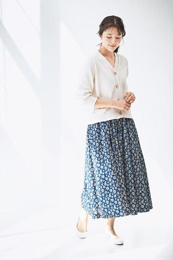 青の花柄スカートに、白のVネックカーディガンを合わせたコーディネートです。パンプスも白で色を合わせて、季節感たっぷりな爽やかコーデにまとめています。カーディガンのボタンを全て留めてトップス風に着こなしていますが、あえてインナーをちらりと覗かせても◎