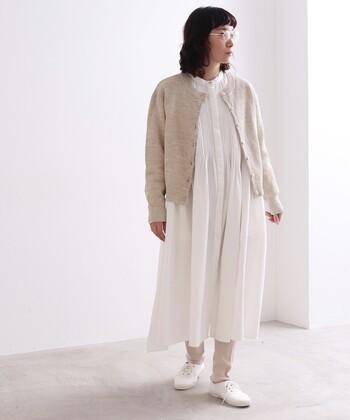 白のシャツワンピースに、ベージュのカーディガンを羽織ったナチュラルなコーディネート。ベージュのレギンスと白のシューズで、2色のみを使って統一感ある着こなしにまとめています。レギンスを靴下に変えても印象が変わりそう。ロングシーズン楽しめるスタイリングです。