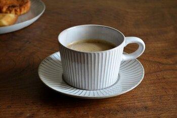 陶土の表面を削ることで、模様をつける技法「しのぎ」を使ったマグカップ&ソーサー。均一につけられたラインがアクセントになり、白地のカップをクラシカルな印象に仕上げています。